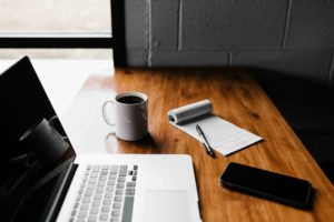 PCやメモ帳が載った机のイメージ