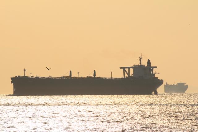 夕焼けの海を航行する大型タンカー