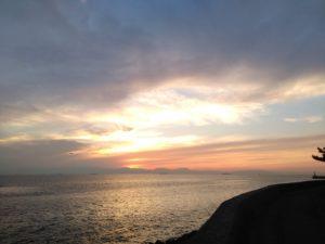 夕焼けで雲と海面がきらめく