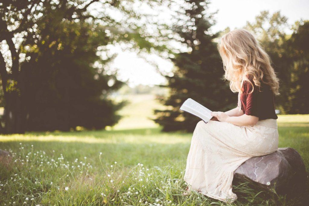 草はらで読書する少女