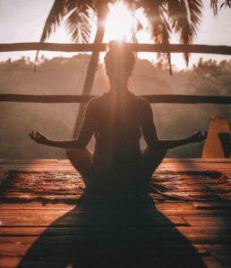 ヨガ瞑想をする女性のシルエット