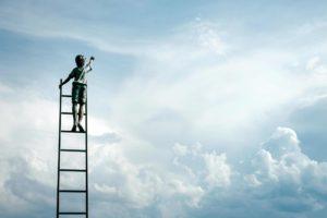 梯子の上で天に向かって手を伸ばす少年