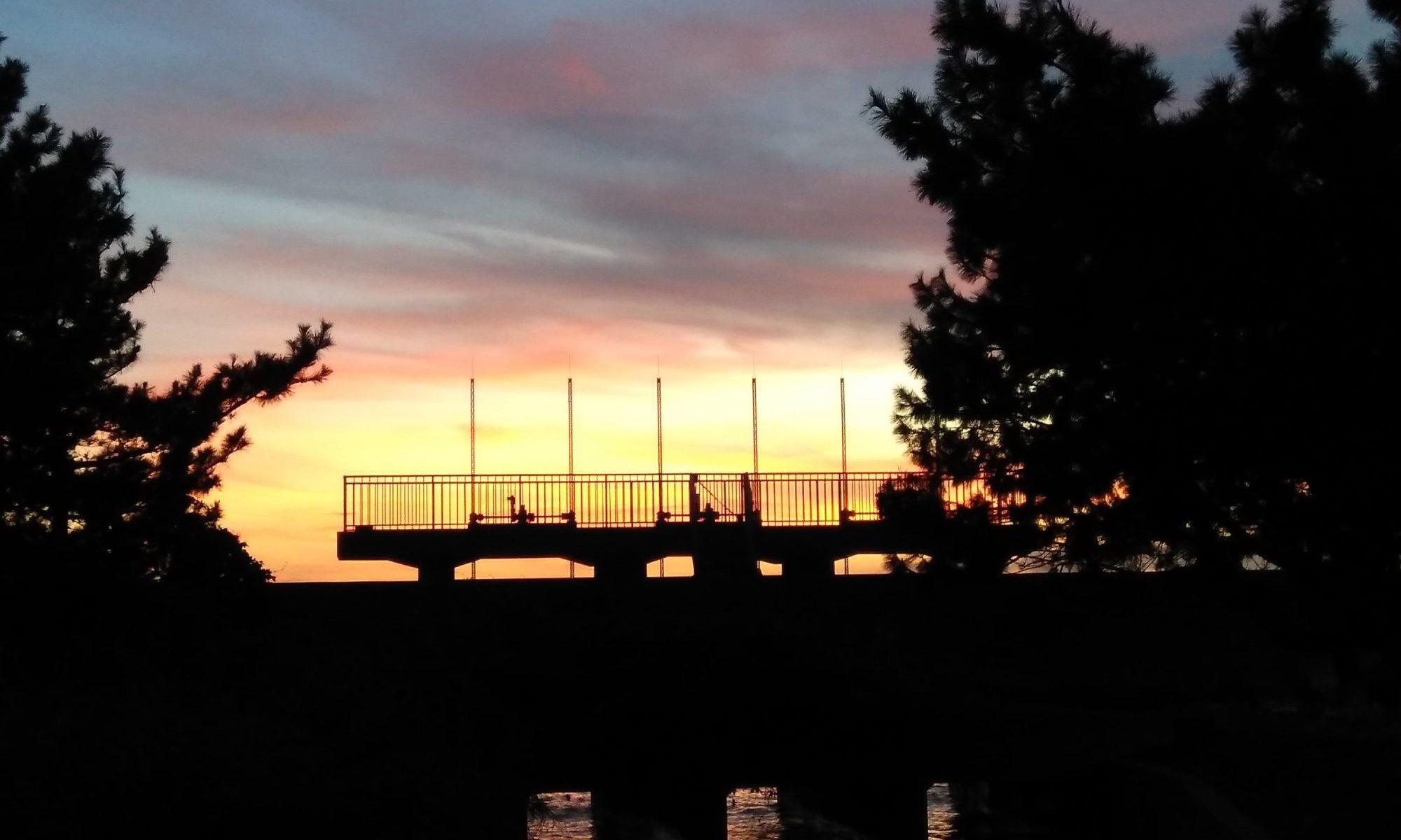 海に続く水門の夕焼けシルエット