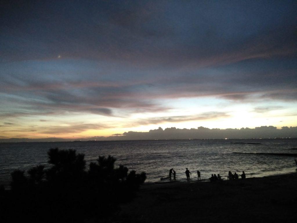 薄暮れ時の海で遊ぶ人々